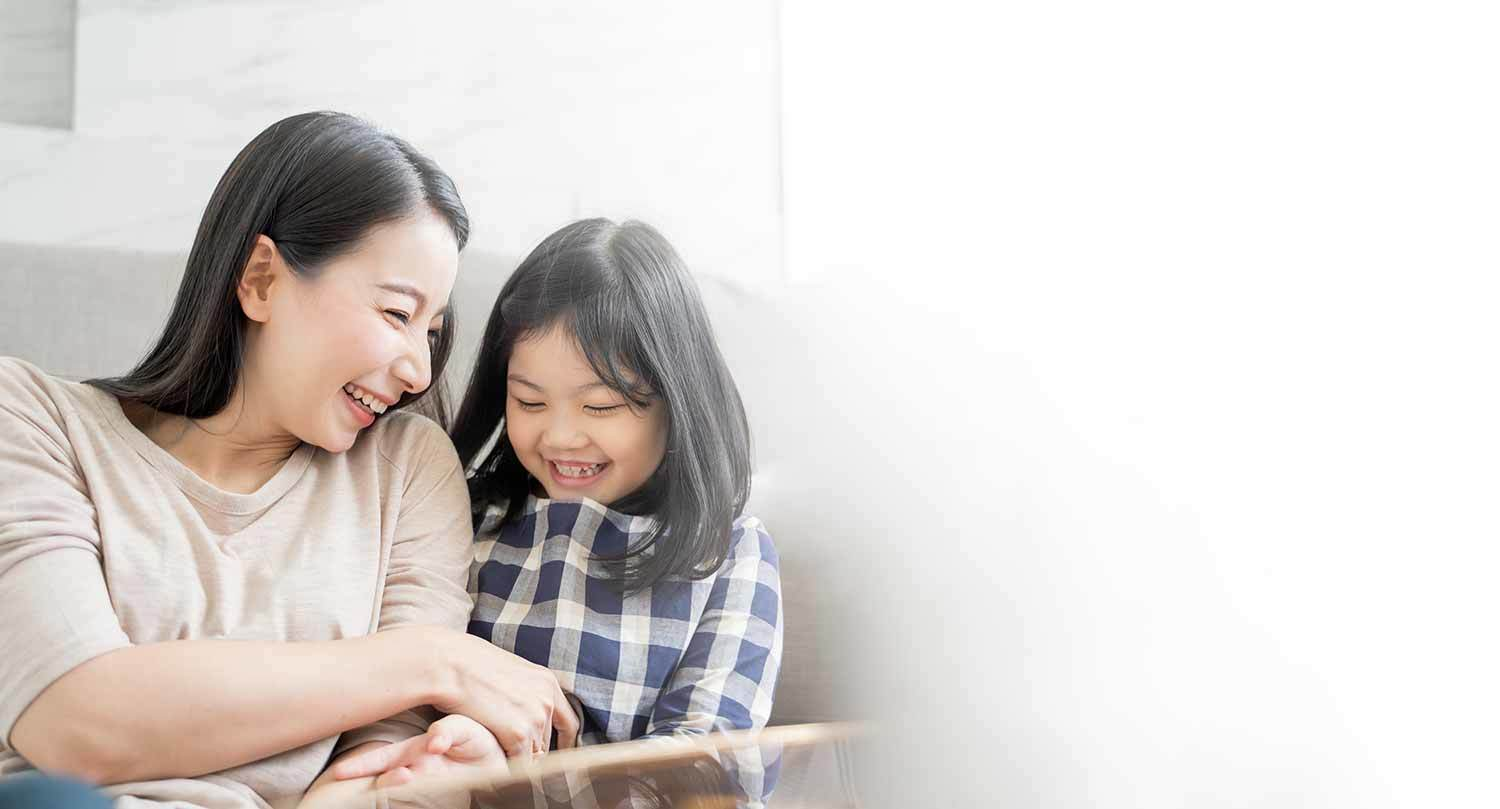 Mother and her daughter child girl playing her mom in sofa living room at home.