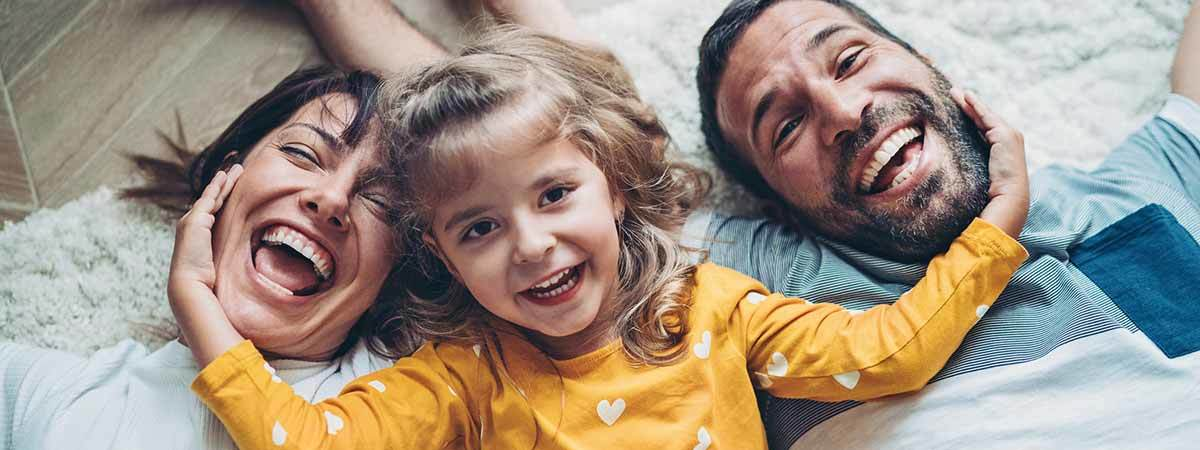Happy family lays on the floor, smiling. Daughter cups her mom and dad's face.