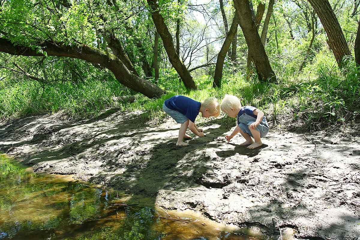 Two toddlers play along the banks of a creek.