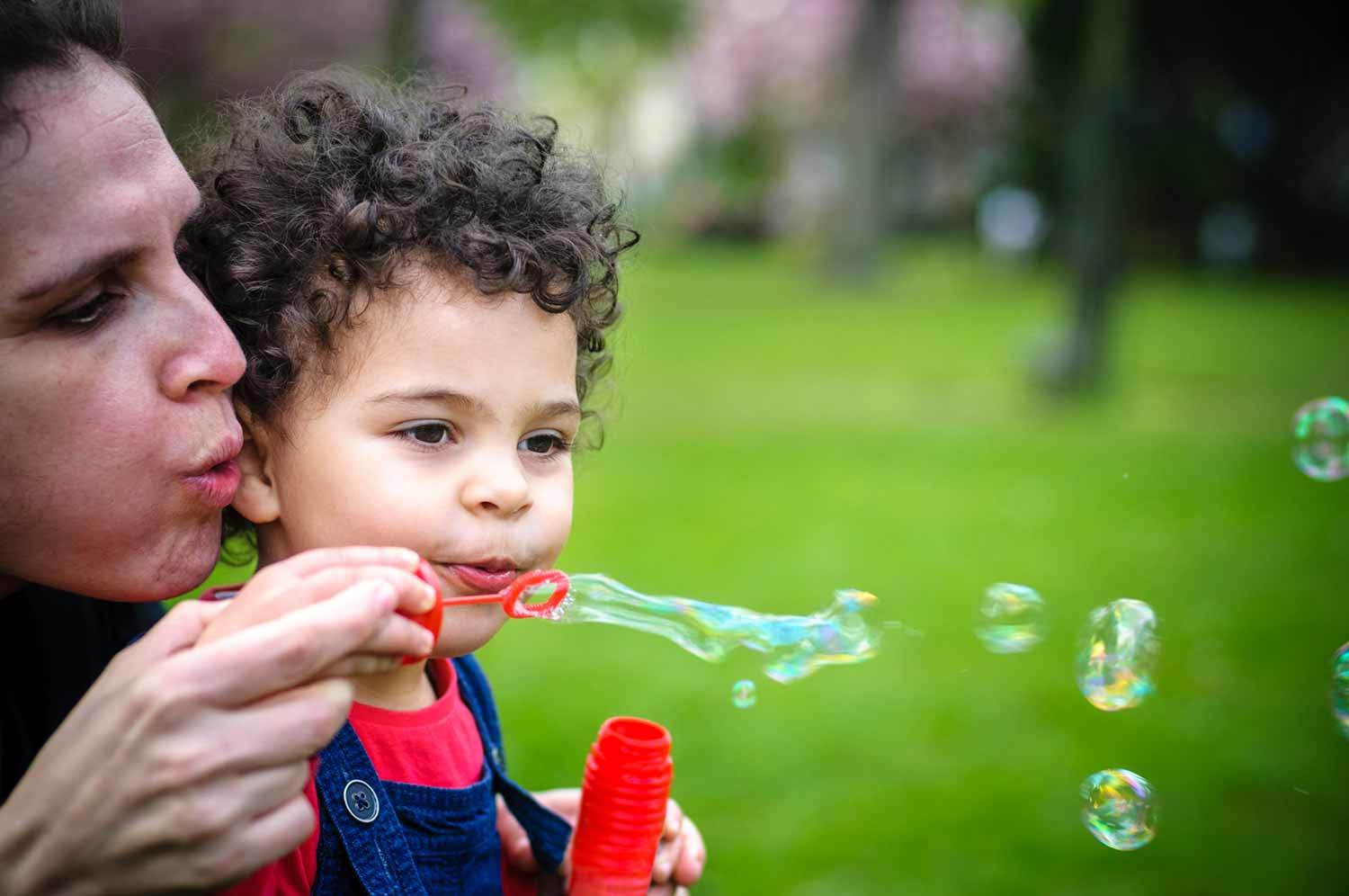 Mom and her young child blow bubbles, outside.
