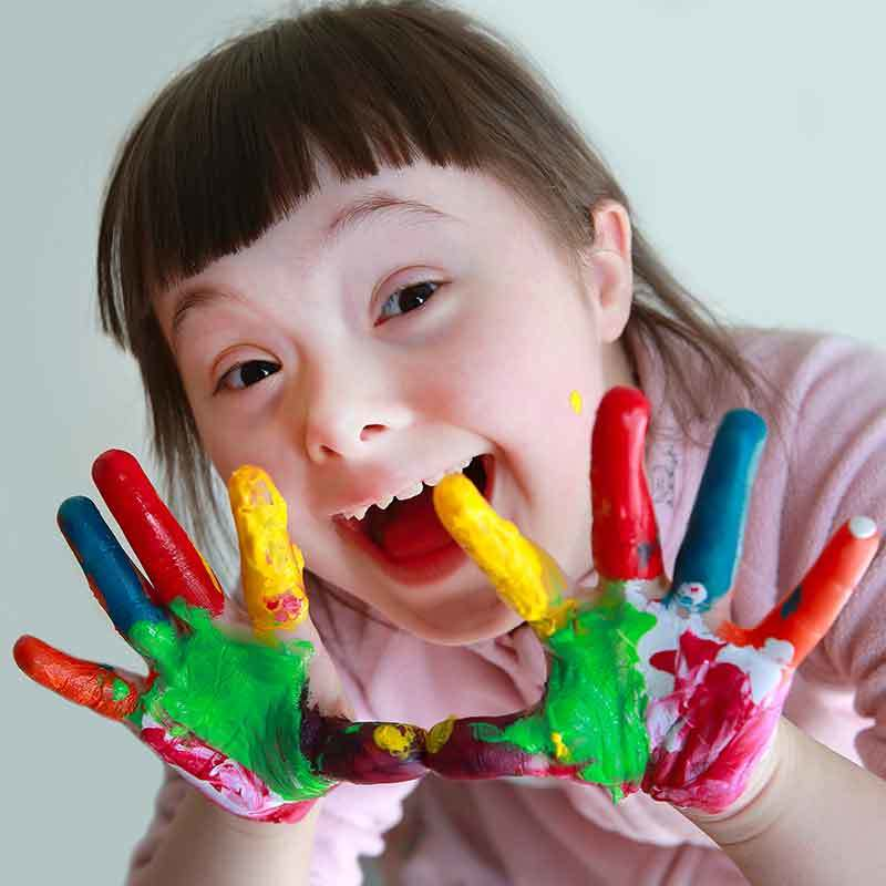 A happy, young girl with down syndrome shows her colorfully-painted hands.