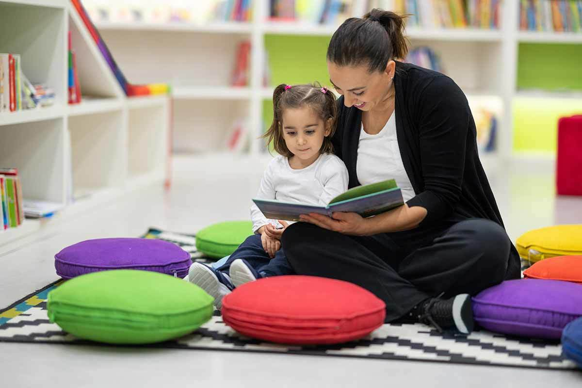 A mother reads to her daughter on the floor of a colorfully-decorated library.